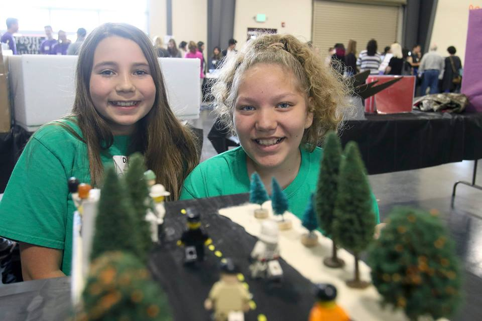Students smile over science project - a model of a forest