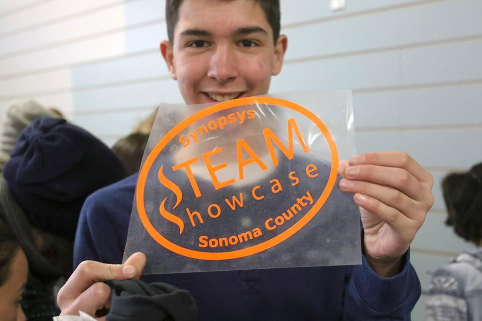 Student holds STEAM Showcase sticker