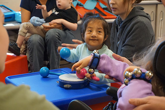 A young preschool girl shakes a rattle during circle time
