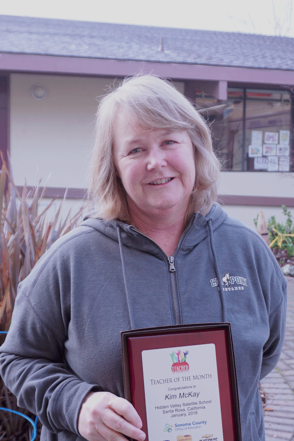 Kim McKay holds her Teacher of the Month Plaque