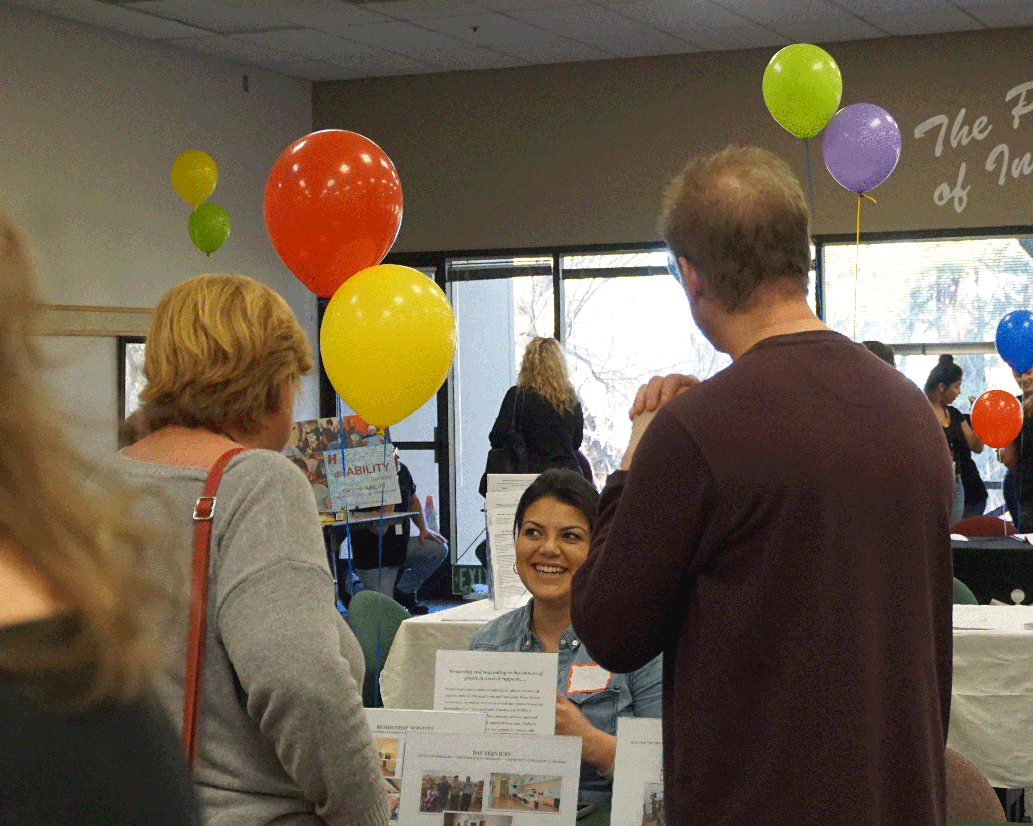 A vendor talks with attendees about services at the Transition Fair