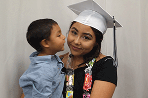 A 2017 graduate hugs her young child