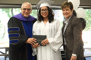 A graduate receives her diploma from the county superintendent and assistant superintendent