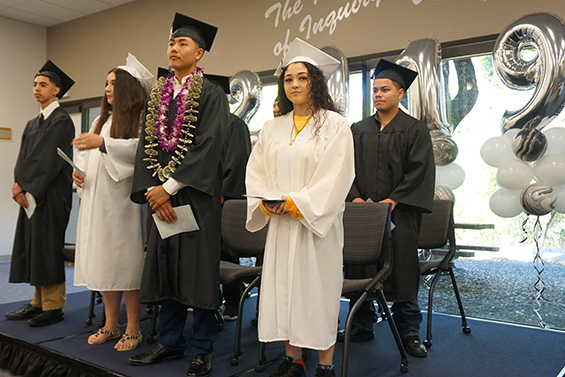 Alternative Education graduates stand with their diplomas