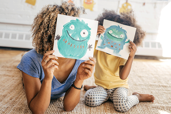 Mother and daughter hold silly drawings