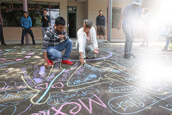 Teacher and students collaborate on chalk project at Elsie Allen.