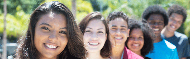 A Latina student smiles at the camera along with other students.