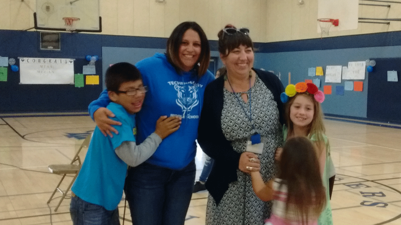 Mrs. Lesser, her daughters, the principal, and a student stand together