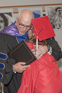 A student graduating from the Transition Program hugs the county superintendent