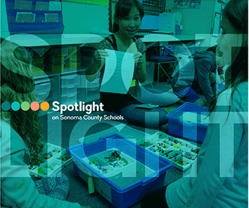 Spotlight cover featuring teacher with students