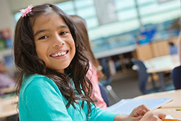 A young girl smiles while seated at a classroom table.