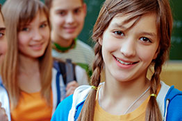 Several young students smile at the camera.