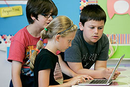 Three young children gather around a laptop computer.