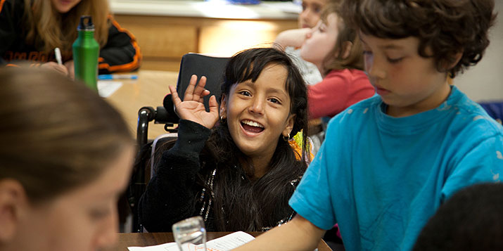 A boy in a wheelchair waves at the camera