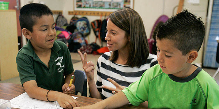 A teacher holds two fingers to show two young boys something.