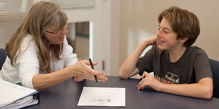 A teacher and student laugh as they discuss something on paper.